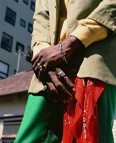 Close up fashion photography of hands wearing silver jewellery clasping in front of green pants and red scarf