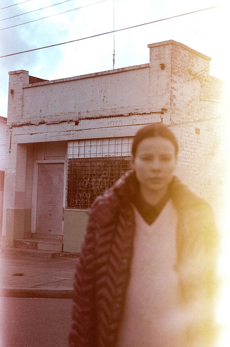 Light leak 35mm film photo with blurred model in puffer jacket and old shop front
