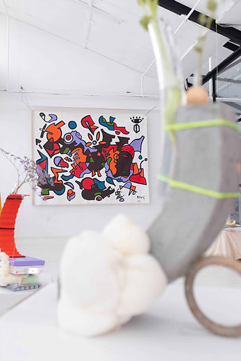 Large coloured canvas painting on the wall with two vase sculptures in the foreground made of cement and found materials