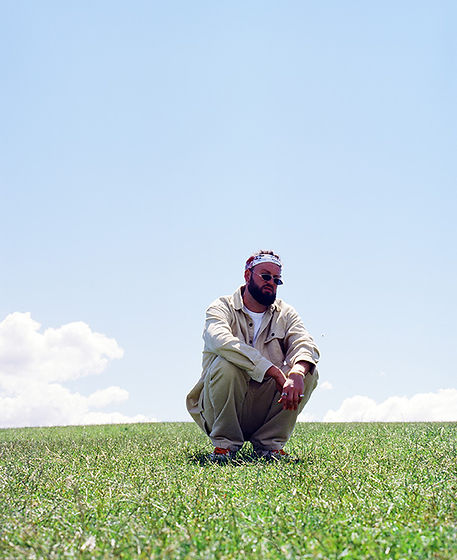 Press photography: Beautiful blue sky with Travy P crouching on a grass field