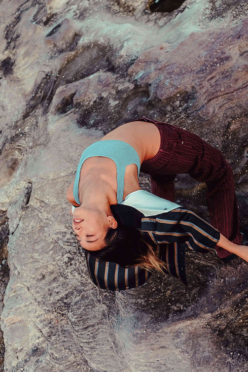 Ethereal editorial photography: Top view of Chinese-Australian model, Jenn, arching her back on Clovelly rocks