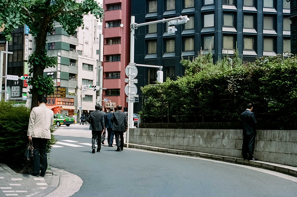 Film Photography: Corporate Tokyo - Two suited men stand again the bushes on their phones while another group walk by