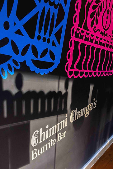 Afternoon light on Chimmi Changa's mural: restaurant name and papel picado