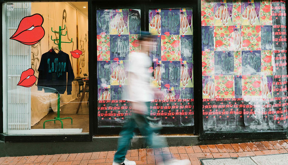 ACC Studio Sydney pop up with windows covered in bright La Ropa posters. A blurry person is walking by in the middle.