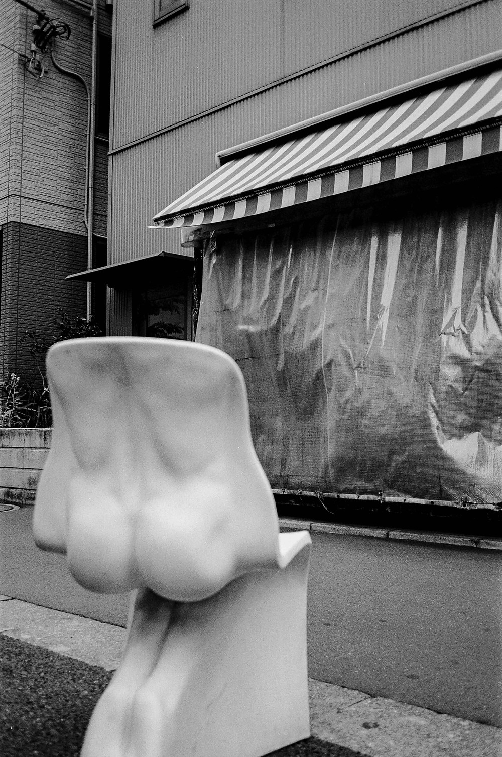 Black and white film photography: A chair with an imprint of a human bum on the sidewalk outside shop stall
