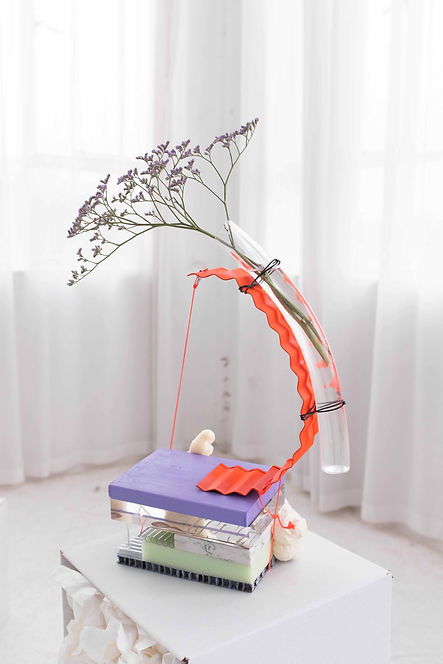 Vase sculpture made of orange corrugated arch shaped galvanised steel, sitting on a lilac wooden and perspex platform