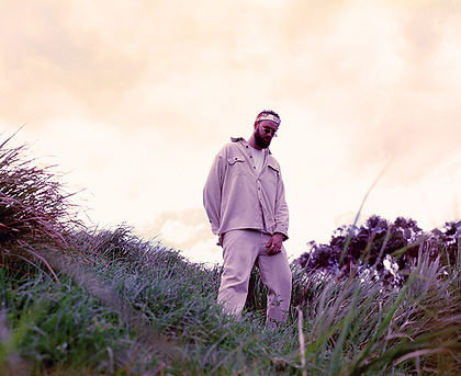 Medium format press photography: Travy P is standing in a field of green and purple grass with peach coloured sky