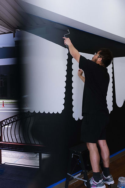 Process of Chimmi Changa's graphic mural by ar–chive: Male artist with black paint roller