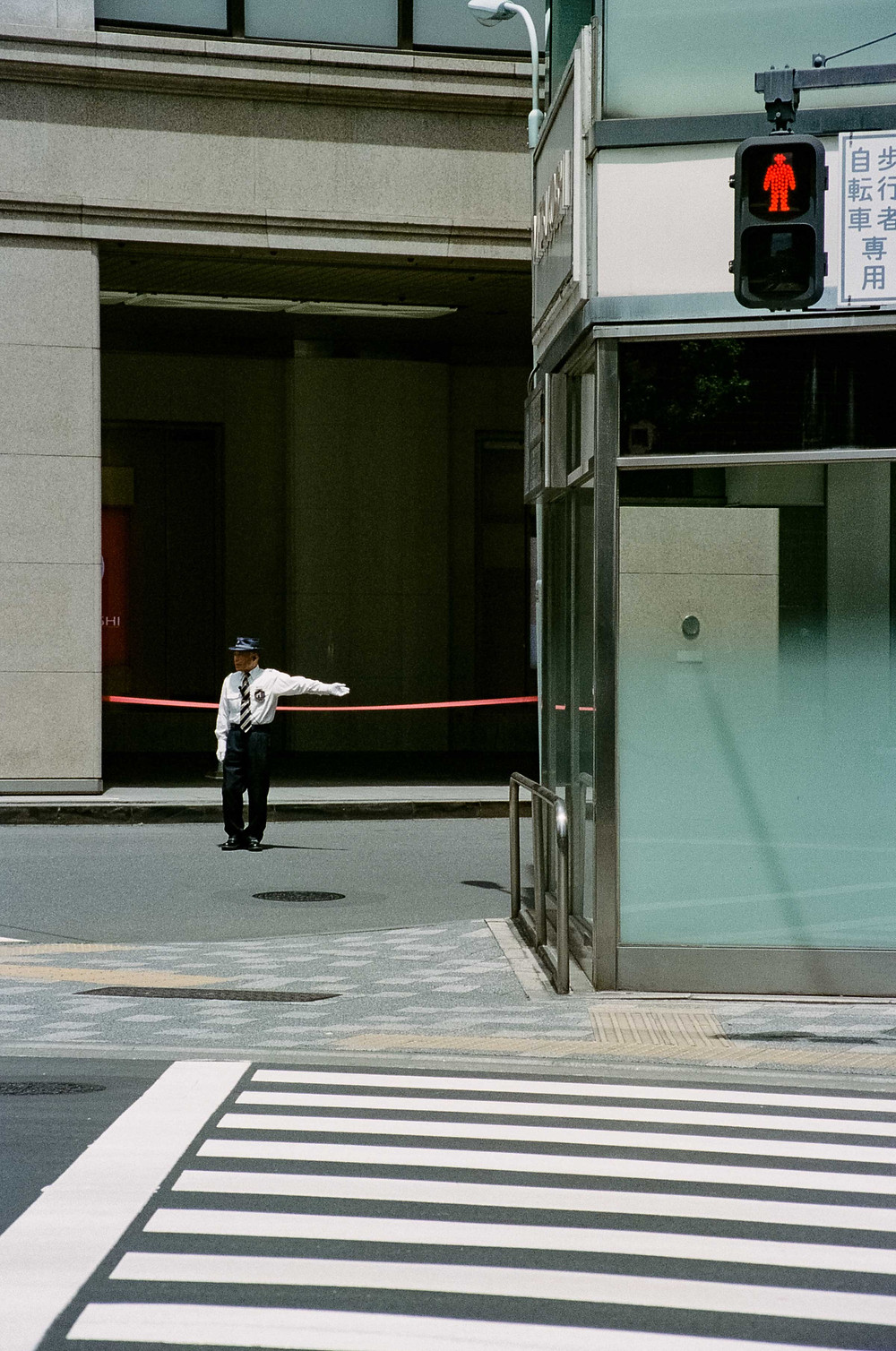 Film Photography: Tokyo street crossing, a security guard has his left hand out directing traffic