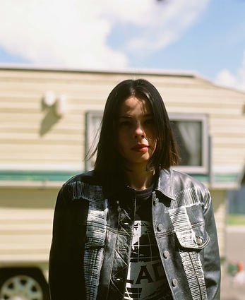 Close up of model in black leather jacket in the shade with caravan in background