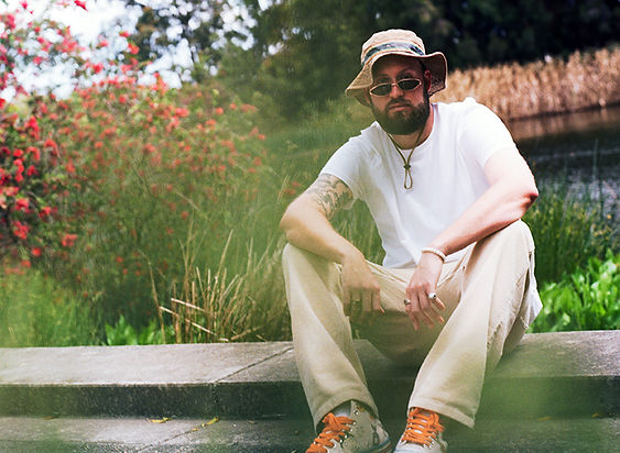 Press photography: Travy P sits in white t-shirt at Sydney Park