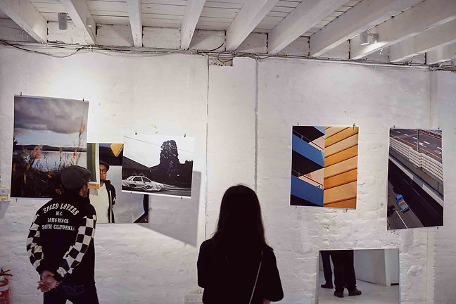Two people at the exhibition. Pictured are photos of the sea, a car in black and white and a blue and yellow geometric wall