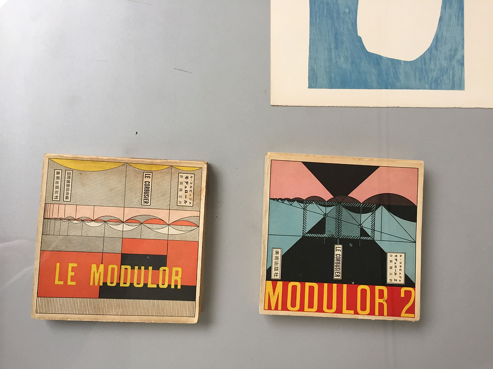 """Two colourful Le Corbusier books on a grey table titled """"Le Modulor"""" and """"Modulor 2"""""""
