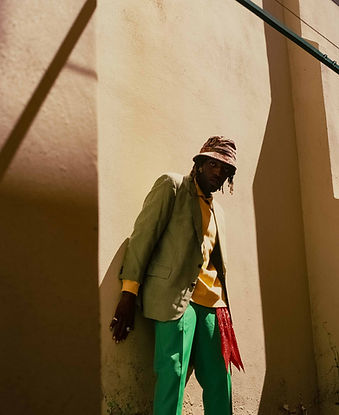 Medium format editorial photography of rapper, IE, in a green suit against a yellow wall with harsh shadows