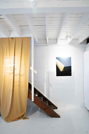 A yellow cotton sheet drapes over the staircase, a perspex sheet reflecting the title of the exhibition, 'Rise To Ubiquity'.