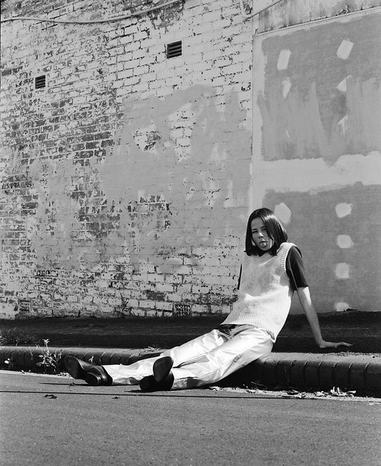 Black and white editorial: Model sits on the kerb in silver pants and black boot.