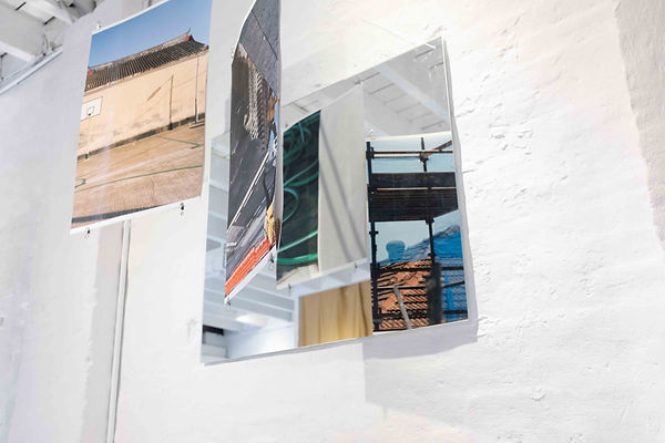 A group of photographs hang in front of a mirror to reveal the back hanging photographs, drawing the viewer in