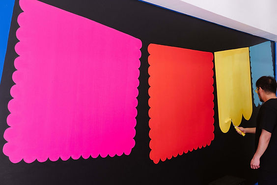 Process of Chimmi Changa's graphic mural by ar–chive: Male artist with yellow paint roller and colour papel picado
