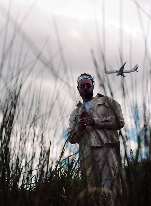 Press photography: Travy P stands in a field of long grass and grey sky with plane flying behind him