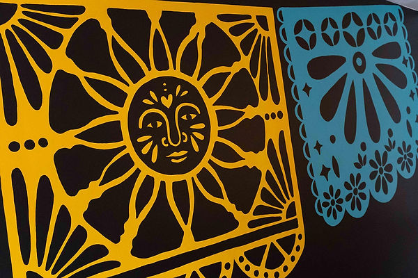 Detail of Chimmi Changa's mural: bright yellow and aqua papel picado with sun and floral design