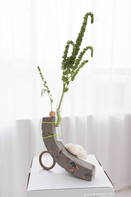 Grey arch-shaped cement vase supported by an upright circular marble ring. Attached is a flower within a clear rubber tube