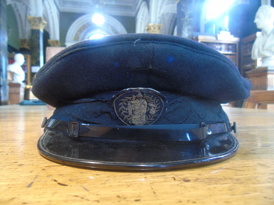 The hat of the doorman's uniform with a badge featuring the crest of the Royal Faculty