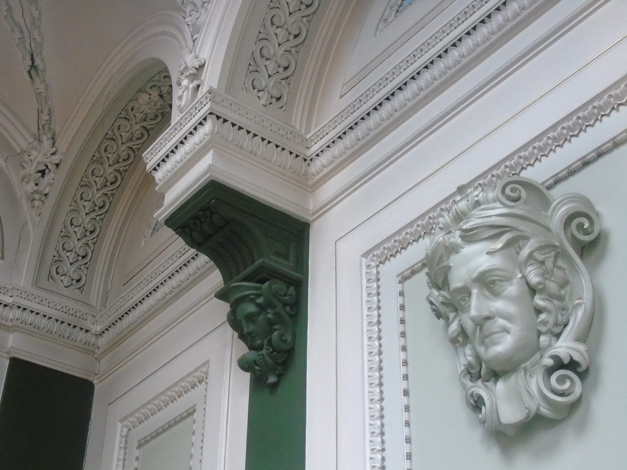 Plasterwork above the staircase, featuring the plaster head of John Millar