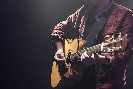 male-musician-playing-acoustic-guitar-in