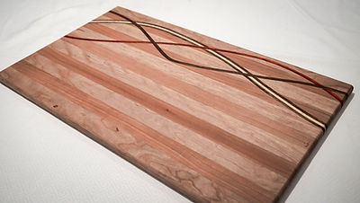 Maple and cherry cutting board with curved through inlay