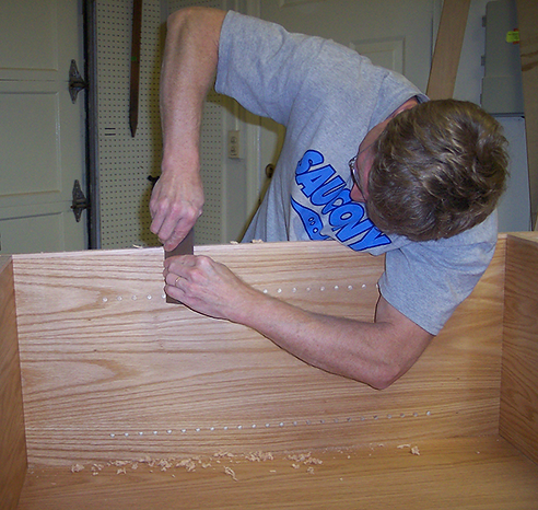 Photo of me working on a cabinet (scraping edge banding)