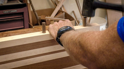 Tapping the dowels into the edge of the cutting board