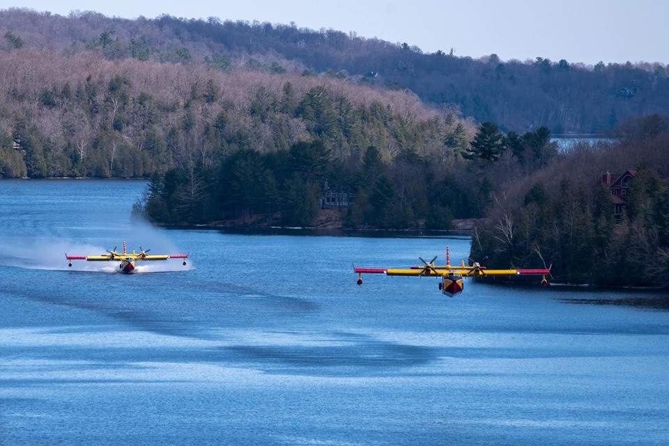 A pair of bombers scooping water from the Gatineau River to fight a fire near Mont Cascades on the afternoon of April 28. Photo courtesy Barbara Havrot