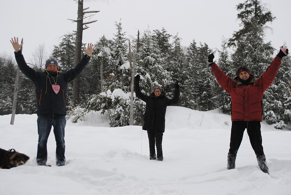 (From left) Stephen Woodley, Carolyn Farquhar and Lyne Daigle raise their hands in celebration (while Woodley's mini-Australian shepherd, Leo, roots around at his feet) as they stand on a frozen beaver pond within the 57-acre Chelsea forest property, which they helped purchase through a community grassroots effort and fundraiser. Hunter Cresswell photo