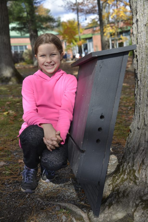 Chelsea Elementary School third grader Bella Smith next to a bat house that she and her classmates built. Photo courtesy Keri George