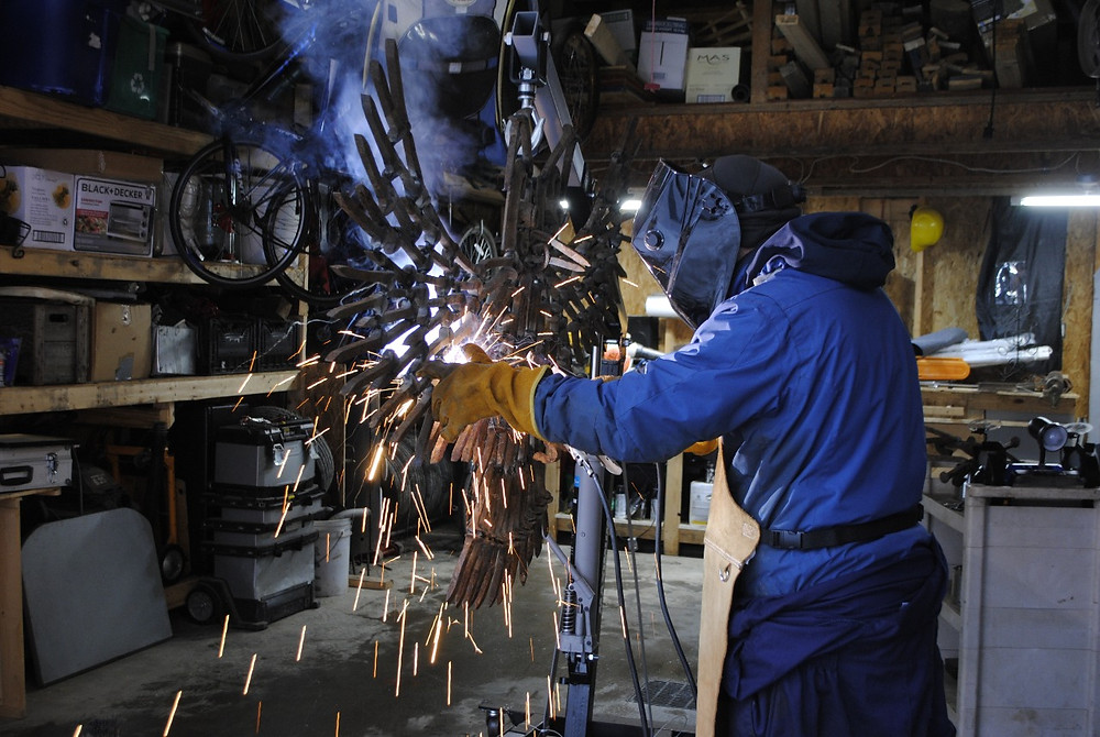 Chelsea metal artist and school teacher Yvan Xavier Regout welding his most recent piece of art, an owl made of scrap metal collected along the old railway in Chelsea. Hunter Cresswell photo