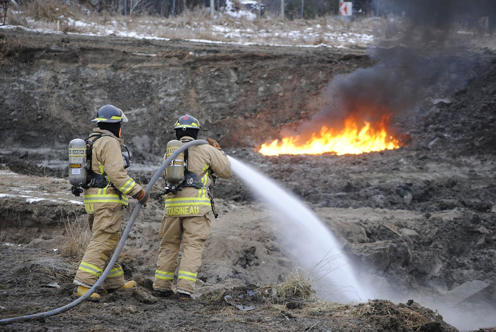 La Pêche Fire Department firefighters Maxime Groulx and Francis Cousineau team-up to hose down fuel-soaked ground near the intersection of Hwy 5 and Chemin Maclaren in Wakefield after an excavator's blade, which was removing decontaminated dirt following a Dec. 7 gas tanker crash, nicked a rock and sparked a blaze on Dec. 11. Hunter Cresswell photo
