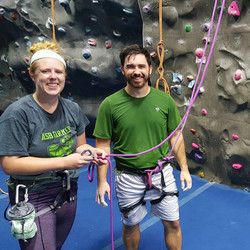 Man and woman rock climbing in a gym