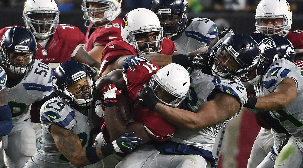 The Seahawks Defense swarms on David Johnson during their matchup on Sunday Night Football. Norm Hall/Getty Images