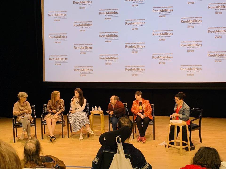Six speakers, including Gail Williamson, Alie B. Gorrie, Kallen Blair, Danny Woodburn, Amy Buchwald, and Christine Bruno sit chairs in front of the ReelAbilities movie screen.