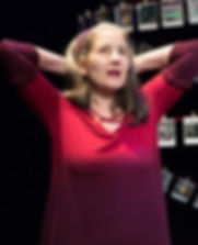 Actress Ann Talman is performing in her play, wearing a fusia dress, in front of a set featuring old family photos.