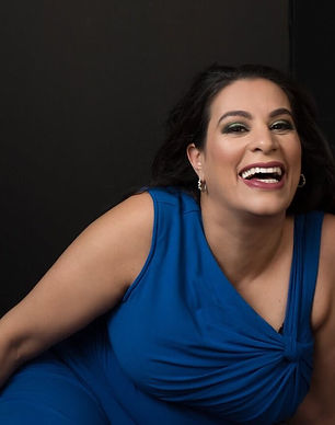 Actress an comedian Maysoon Zayid smiles and weas a blue dress against a dark background.