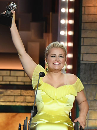Tony Winner Ali Stroker is smiling, wearing a yellow dress, and holding up a Tony award statue directly after receiving the award. She is using a wheelchair.