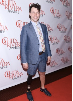 "Evan Ruggiero stands in front of a ""step and repeat""at the Chita Rivera awards."