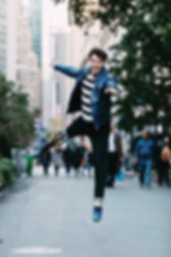 One-legged dancer Evan Ruggiero jumps up on leg wearing one blue tap shoe and a prosthetc leg in the streets of New York City,