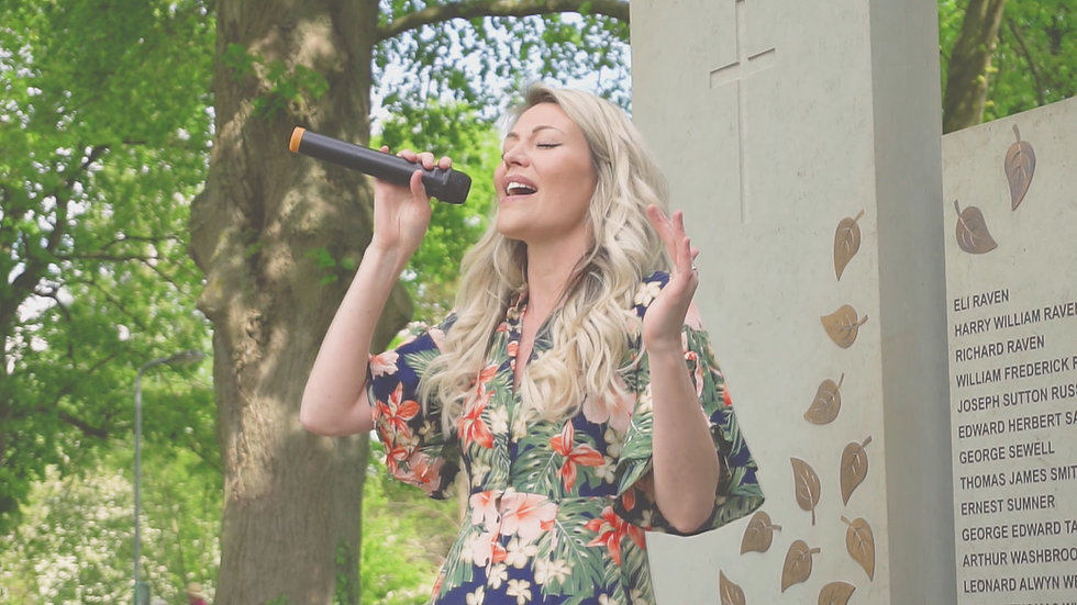 A woman holding a microphone and singing in front of a village war memorial that is surrounded by trees