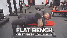 A man performing a chest press exercise using a flat bench in a gym