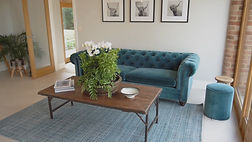 A square brown table with green flower arrangement next to a teal blue sofa from inside a barn conversion house