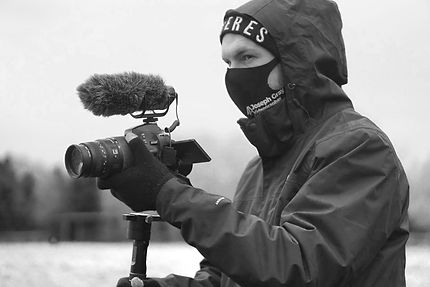 A man using a Nikon DSLR Video camera with a Rode Microphone outside in the snow. The environment is very harsh and the man is wearing a black north face coat, a mask and a hat