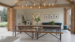 Long brown rectangular table with pretty industrial lights hanging from the ceiling of a kitchen inside of a barn conversion on a farm
