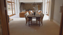 A living room with a long brown rectangular table, brown chairs and orange sofas from inside a barn conversion house